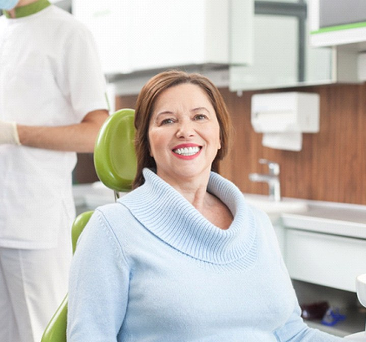 A middle-aged woman wearing a light blue sweater sits in a dentist's chair preparing for teeth cleaning in Wichita Falls