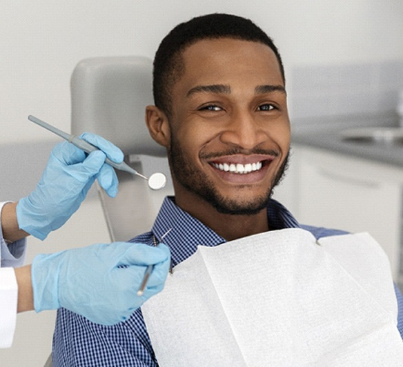 A young man smiles in preparation for a dental checkup during his visit