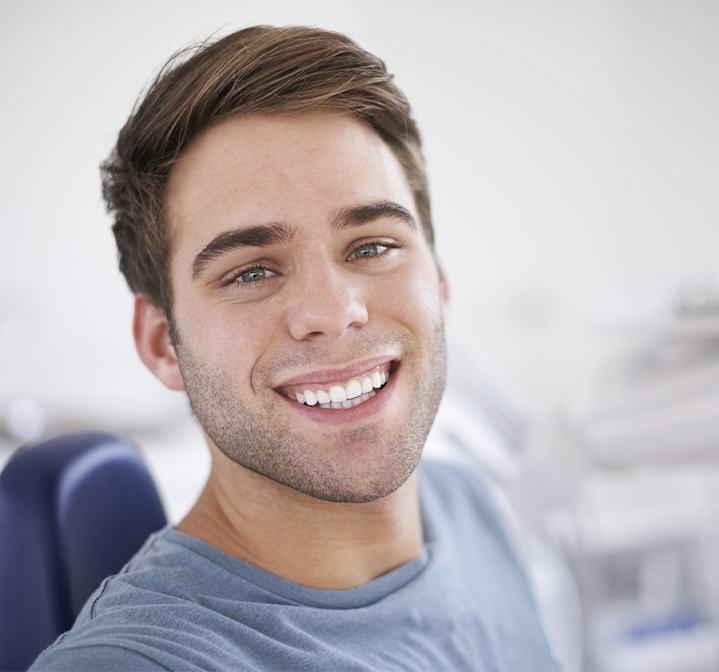 Young man smiling after wisdom tooth extraction