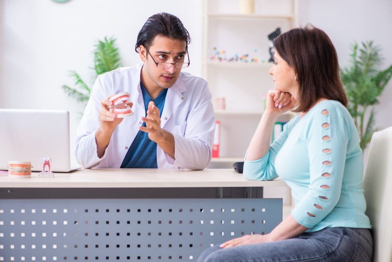 a dentist and patient discussing the effects of dark-colored beverages and what can happen to teeth over time