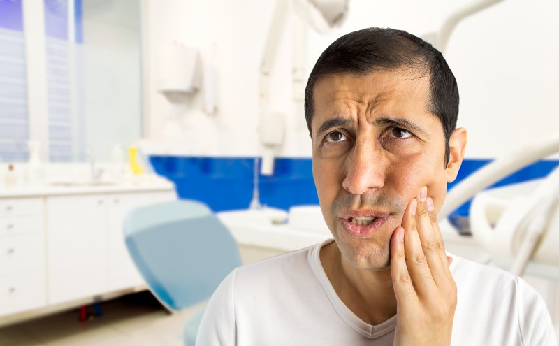 Man in dental office rubbing his jaw in pain