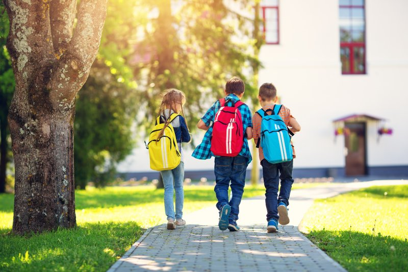 Children wearing backpacks while walking into school