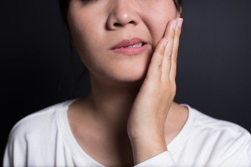 young woman holding jaw after wisdom tooth removal